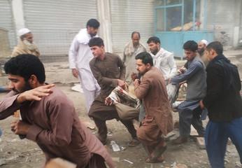 Afghan men carry an injured man after a blast in Jalalabad, Afghanistan