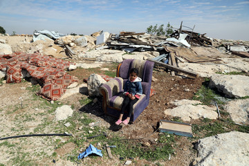 Palestinian girl sits on a couch after Israel troops destroyed a Palestinian structure in the village of Al-Eizariya, in the occupied West Bank