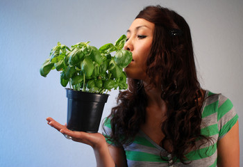 Asian Woman holds a basil in their hand