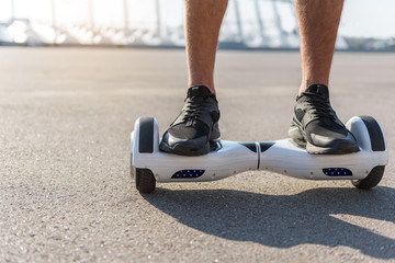 Close up male feet wearing modern sneakers going on hoverboard at street. Copy space