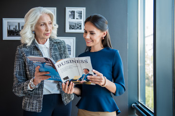 Interesting article. Successful stylish senior woman is standing with her young cheerful female colleague in office. They are holding business magazine and reading while expressing gladness