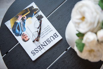 Popular journal. Close-up top view of black coffee table with glasses, business magazine and vase with white flowers are on it