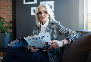 Reading news. Portrait of stylish attractive optimistic mature businesswoman in glasses is holding journal and looking at camera with slight smile while sitting on couch in office
