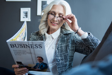 Enjoying business news. Joyful stylish gray-haired elegant woman in glasses is reading journal with smile. She is sitting on couch in cozy office and expressing gladness