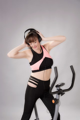 Woman holding headphones with an exercise bicycle against a grey background