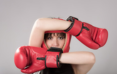 Woman wearing boxing gloves and a red headguard