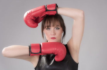 Woman wearing a black leather top and red boxing gloves