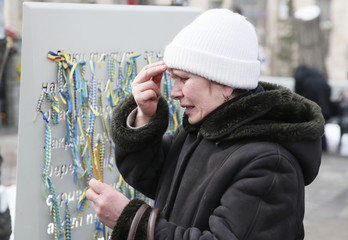 A participant holds candles during a commemoration ceremony at the monument to the people killed during the 2014 Ukrainian pro-European Union protests in Kiev