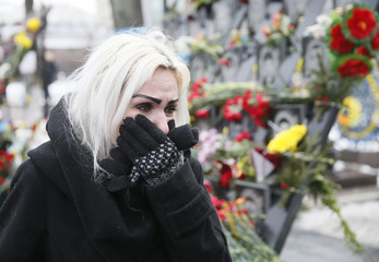 A woman reacts during a commemoration ceremony at the monument to the people killed during the 2014 Ukrainian pro-European Union protests in Kiev