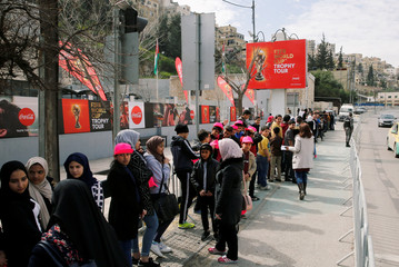 Football fans wait in line to see the FIFA world cup trophy during Trophy Tour, in Amman