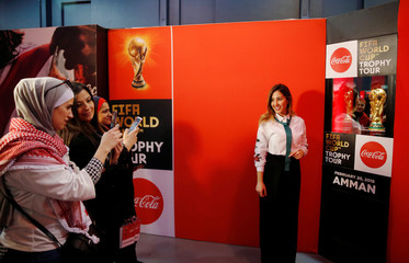 Football fans pose for photographs during the Fifa World Cup Trophy Tour, in Amman