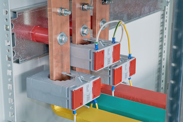 Copper busbars with current transformers on them in an electric Cabinet. Copper busbars are bolted to the mounting panel. Marking on wires and bus bars of red, green and yellow.