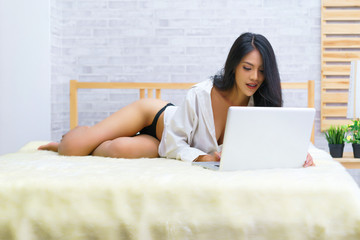 Sexy asian woman lying on bed with laptop computer at home. concept of relax holiday and comfort.