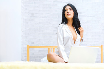 Sexy asian woman sitting on bed with laptop computer at home. concept of relax holiday and comfort.