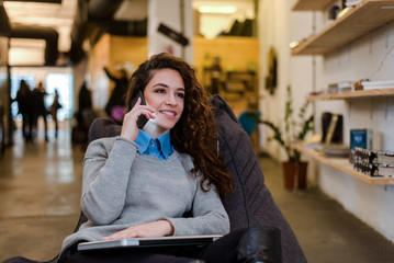 Beautiful caucasian woman talking on phone in the modern environment.