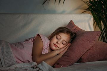 portrait of adorable kid sleeping on sofa at home