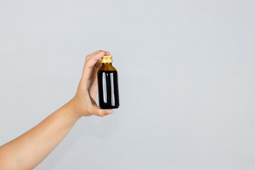 Hand holds syrup for cough throat on isolated on white background.