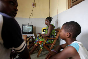 Jean-Noel Kouame, 31, sits with his family as they watch television inside their house, on the outer limits of the main city Abidjan's vast urban sprawl