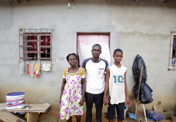 Jean-Noel Kouame, 31, poses with his family outside his house, on the outer limits of the main city Abidjan's vast urban sprawl