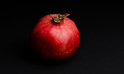 Fresh red pomegranate on a black background