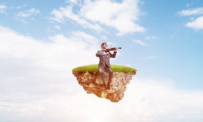 Handsome violinist on floating island in blue sky play his melody