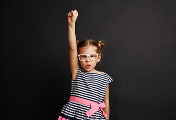 Cute girl wearing spectacles standing with hand up like superhero. Studio portrait of little child winning success.