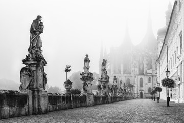 Statues in front of misty St. Barbara's Church in Kutna Hora, Czech Republic