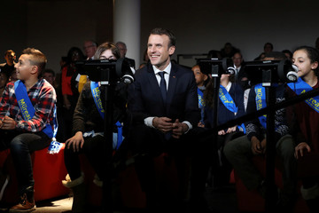 """French President Emmanuel Macron sits with children at the digital museum """"Micro-Folie"""" as he visits a mediatheque in Les Mureaux"""
