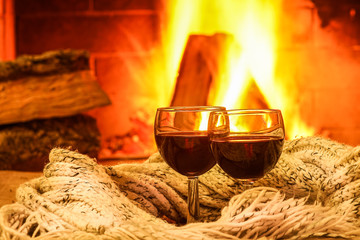 Glasses of red wine against cozy fireplace background, winter vacation.
