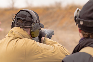 Male training with pump action shotgun  outdoors in field.