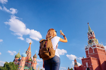 Travel and techology. Young woman taking photo on her smartphone on Red Square in Moscow, Russia.