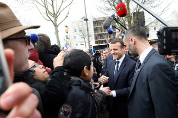 French President Emmanuel Macron greets people after a visit at a mediatheque in Les Mureaux, Paris suburb