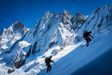 Young man climbing up on glacier in big mountain, massive Mont Blanc, Chamonix