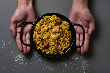 man with a typical spanish paella valenciana