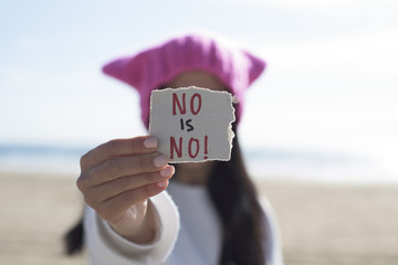 woman with a pink hat and the text no is no