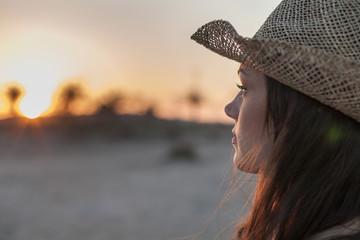 Portrait of woman wearing straw hat looking away