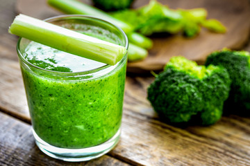 Green vegetable smoothie in glass at wooden background