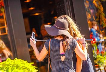Woman taking selfie using selfie stick