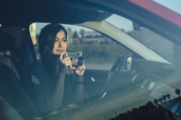 Portrait of girl taking photos from car with vintage camera and glass reflection