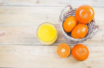 Fresh oranges in basket and a glass of fresh orange juice on wooden background.