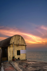 A view of generator room by the lighthouse during the sunset