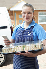 Portrait Of Female Caterer Delivering Tray Of Sandwiches To House Checking Text Message On Mobile Phone