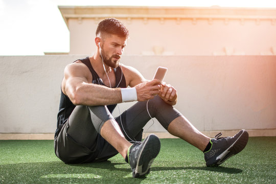 Young handsome man using phone while having exercise break in rooftop gym.