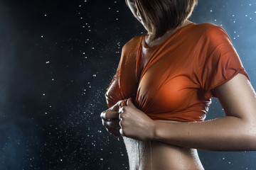 Torso of a big breasted girl wearing wet shirt on a dark background with falling rain drops and scenic smoke.