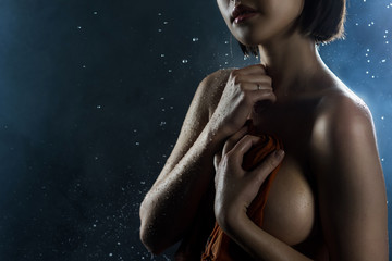 Beautiful big breasted girl covers herself with a wet shirt on a dark background. Falling rain drops and artistic scenic smoke.
