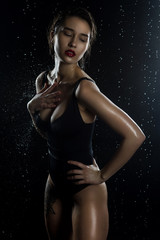Beautiful wet big breasted girl wearing black swimsuit on a dark background. Falling rain drops and artistic scenic smoke