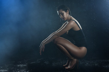 Beautiful asian wet big breasted girl wearing black swimsuit squats on a dark background. Falling rain drops and artistic scenic smoke