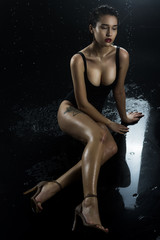 Beautiful asian wet big breasted girl wearing black swimsuit sitting on the wet floor on a dark background