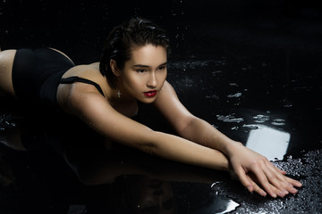 Beautiful asian wet big breasted girl wearing black swimsuit lays on the wet floor on a dark background. Falling rain drops and artistic scenic smoke