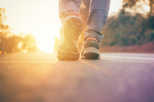man walking on road with sun light flare ,close up on shoe jogging workout wellness after work